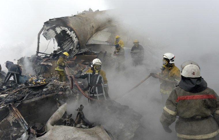 Image: Kyrgyz firefighters work among remains of a crashed Turkish Boeing 747 cargo plane