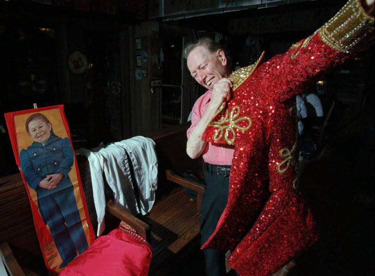 Image: Harold Ronk, the original singing ringmaster for Ringling Bros. tries on one of his original robes in Farmington, Illinois, May 16, 1996.