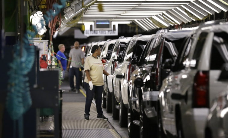 Image: An auto worker inspects finished SUVs coming off the assembly line at the General Motors auto plant in Arlington, Texas on May 13, 2014.
