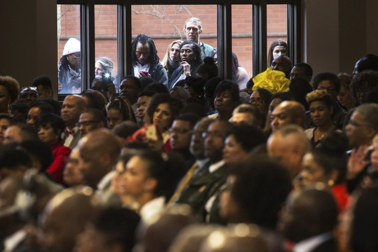 Image: People watch the Rev. Martin Luther King Jr. holiday commemorative service at Ebenezer Baptist Church through a window on Jan. 16 in Atlanta, Georgia.