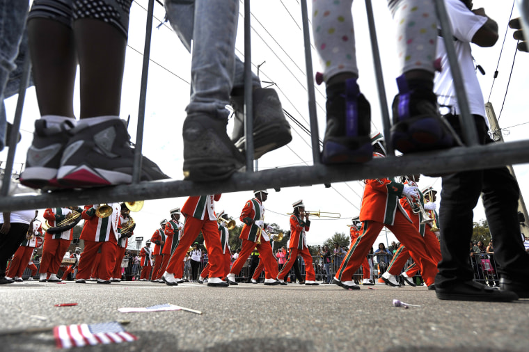 Image: Children stand on the parade route railings to watch Jones High School Marching band perform during the Martin Luther King Jr., Day parade in Tampa, Florida on Jan. 16.