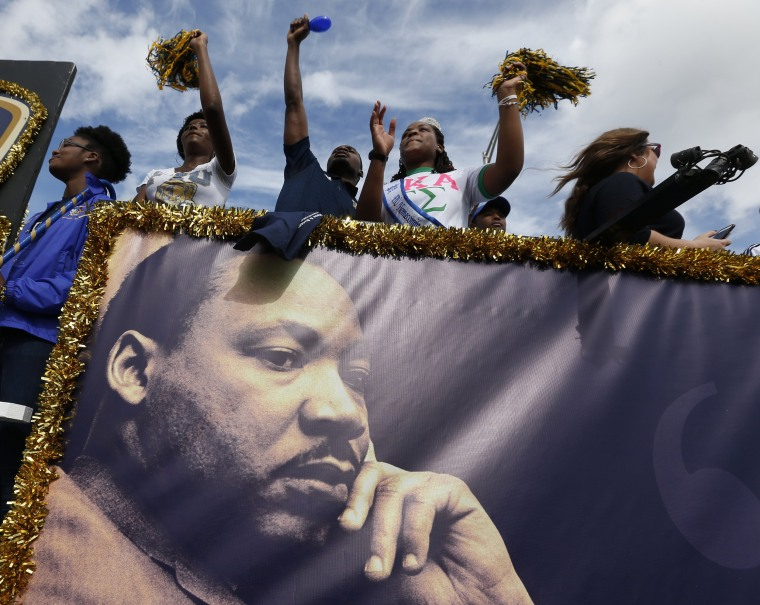 Image: People aboard a float from Florida International University wave to the crowd during a parade honoring Dr. Martin Luther King Jr on Jan. 16 in the Liberty City neighborhood of Miami, Florida.