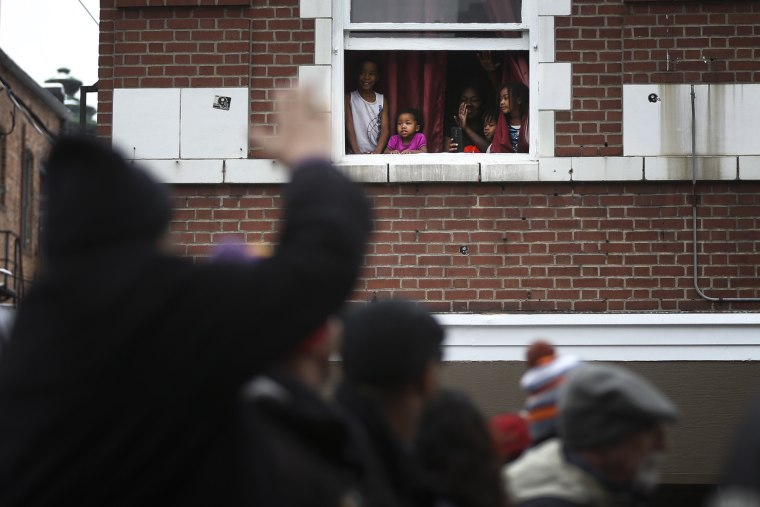 Image: Children look on and wave as the Martin Luther King Jr. parade passes by on Jan. 16 in Denver, Colorado.