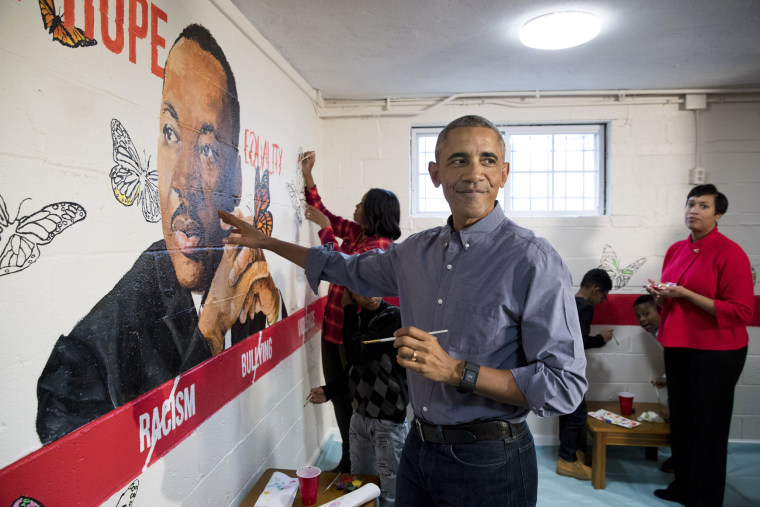 Image: President Barack Obama and First Lady Michelle Obama help paint a mural depicting Martin Luther King Jr., as Mayor of Washington, D.C. Muriel Bowser, right, looks on, at the Jobs Have Priority Naylor Road Family Shelter on Jan. 16 in Washington, D.