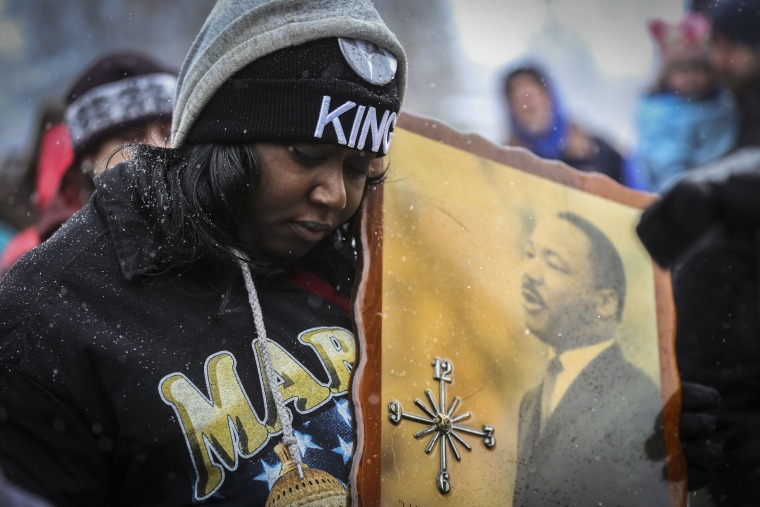 Image: Bridget Johnson holds a sign while a prayer is recited at the Martin Luther King parade in Denver, Colorado on Jan. 16.