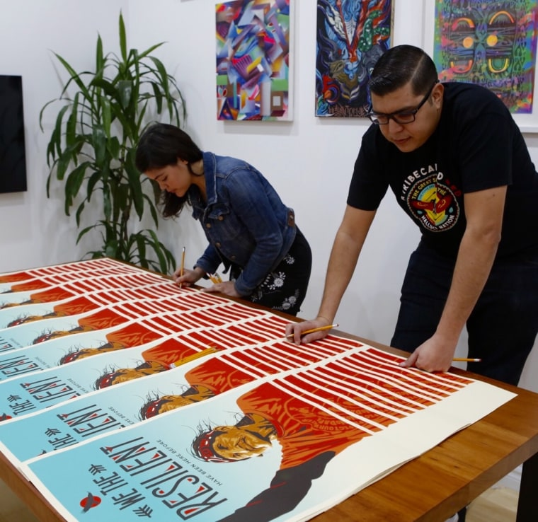 "Artists Ernesto Yerena and Ayse Gursoz signing one of the posters in the ""We the People"" art series."