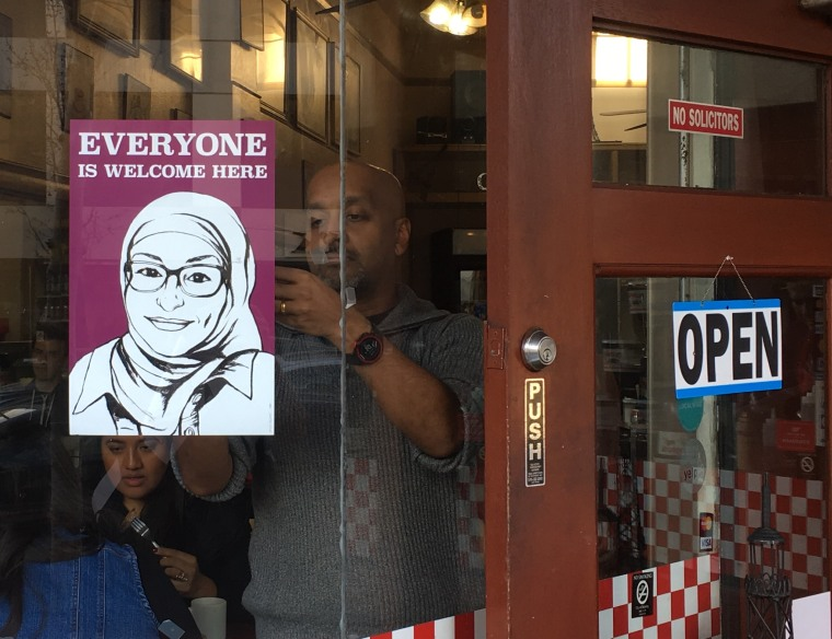 """Berkeley, CA residents hang up signs as part of a campaign declaring \""""Everyone is welcome here.\"""""""