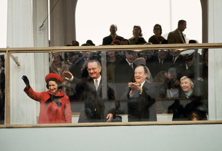 Image: Lady Bird Johnson, President Lyndon Johnson, Vice President Hubert Humphrey and Mrs. Humphrey wave and clap as they watch the inaugural parade from behind protective glass in Washington, D.C. in Jan. 1965.
