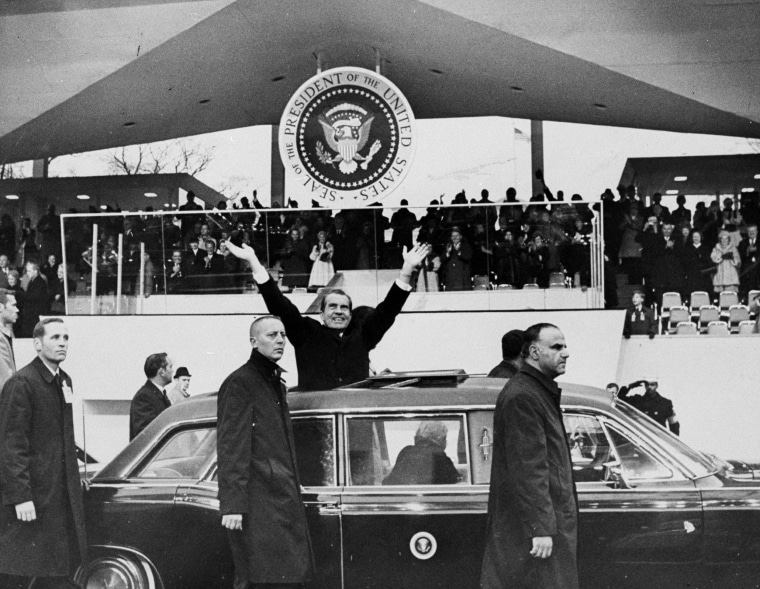 Image: President Richard Nixon stands in car during the inaugural parade on Jan. 20, 1969.
