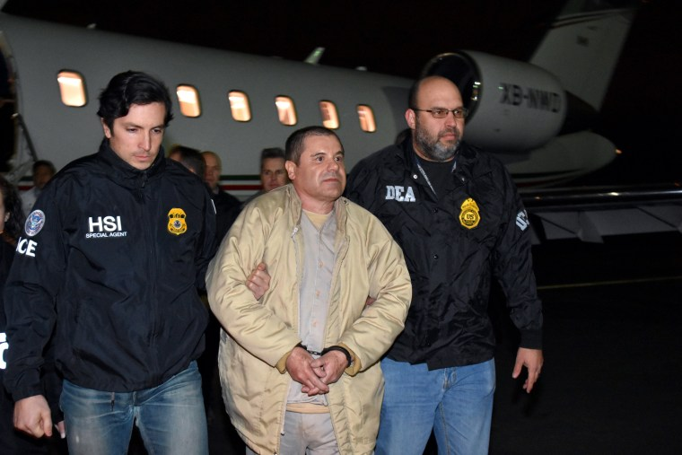 """Image: Joaquin \""""El Chapo\"""" Guzman is escorted from a plane to a waiting caravan of SUVs at Long Island MacArthur Airport on Jan. 19 in Ronkonkoma, New York."""