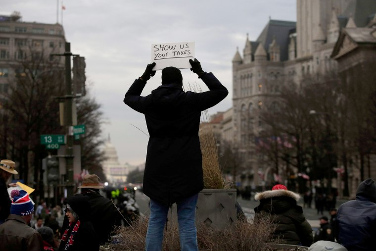 Image: A person holds up a sign at Freedom Plaza prior to the start of the inauguration.