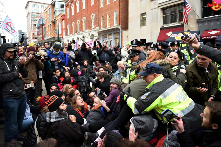 Image: Police help people who try to attend the inauguration parade but are blocked by demonstrators sitting down at 10th Street near Pennsylvania Avenue to prevent spectators from reaching one of the entrances to the parade route to protest Trump.
