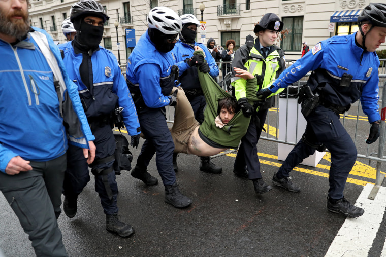 Image: A protester is dragged away from a public access point to the National Mall on 14th Street NW prior to the inauguration.