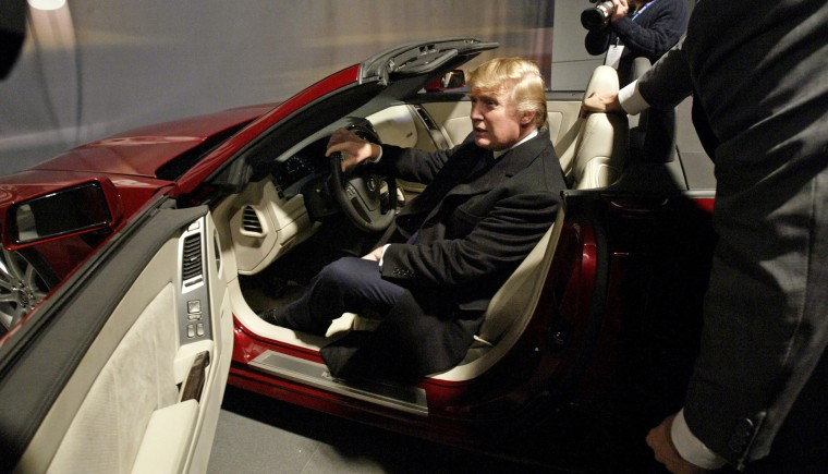 Donald Trump sits in the seat of the 2006 Cadillac XLR-V at the Auto Show in New York in 2005. Trump stopped by the Cadillac display to pick up his keys for his 2006 Cadillac DTS executive limousine.