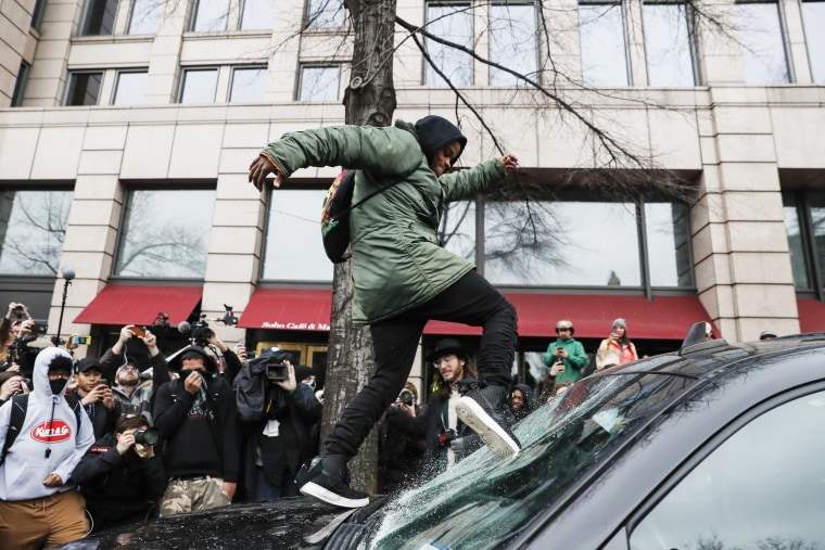 Image: A protester kicks in a windshield during a demonstration in Washington, D.C on Jan. 20 after the inauguration of President Donald Trump.