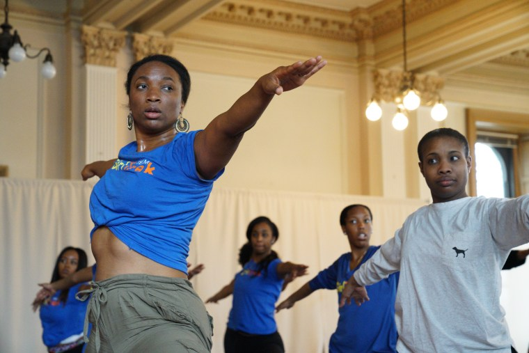 GirlTrek cofounder T. Morgan Dixon (tied shirt) does Trap Yoga led by Brandon Copeland at GirlTrek's day of #BlackGirlHealing event in Washington D.C.