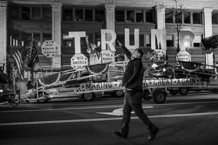Image: A man gestures as a vehicle with Donald Trump's propaganda tours the city ahead of the presidential inauguration on Jan. 19.
