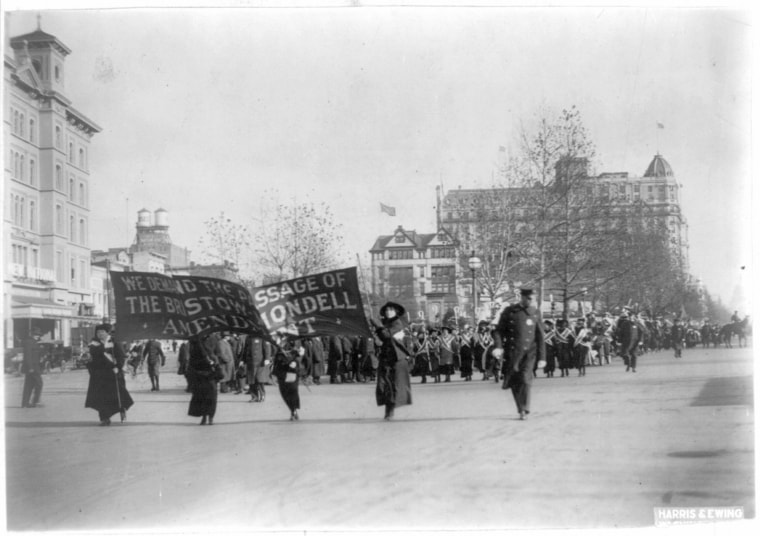 """Image: Four women lead a march of thousands, holding a banner that says, \""""We demand the passage of the Bristow-Mondell amendment,\"""" at the women's suffrage parade in Washington on March 3, 1913, one day before the inauguration of President Woodrow Wilson."""