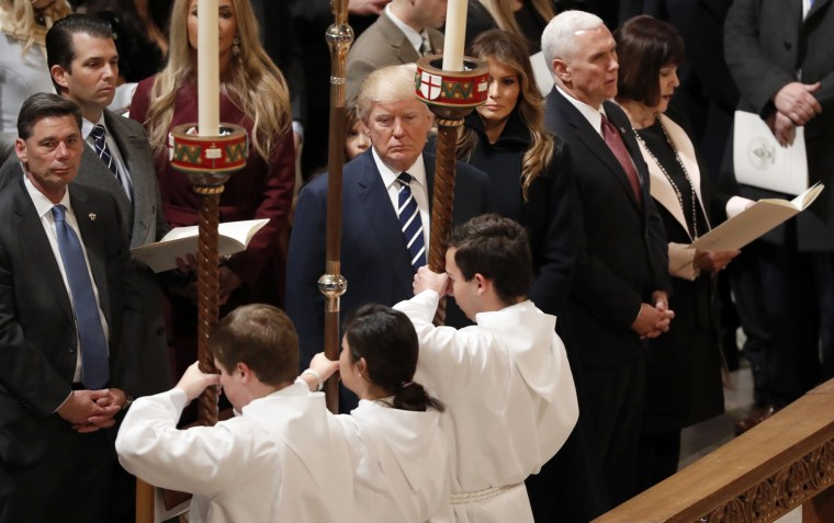 Image: President Trump watches acolytes carrying candles as they pass while he is accompanied by Melania, Vice President Mike Pence and his wife Karen (R), during a prayer service the morning after his inauguration, Jan. 21.