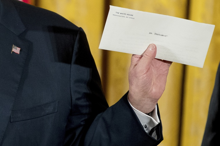 Image: President Trump holds up a letter left for him by former President Barack Obama as he speaks at the swearing in ceremony.