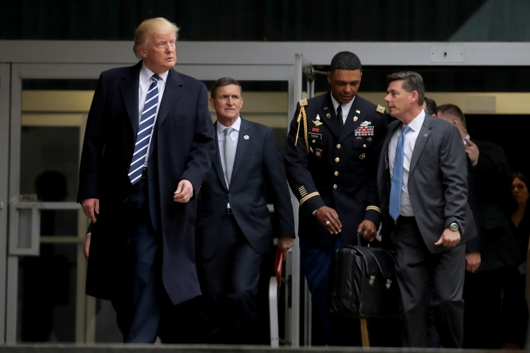 Image: Trump leaves the CIA headquarters accompanied by National security adviser General Michael Flynn (2nd L) after delivering remarks.