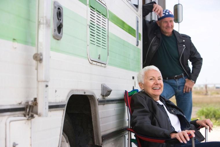 Happy senior couple outside RV camper