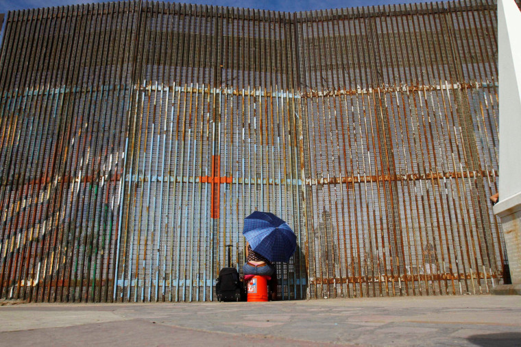 Image: A woman talks to her relatives across a fence separating Mexico and the United States, in Tijuana