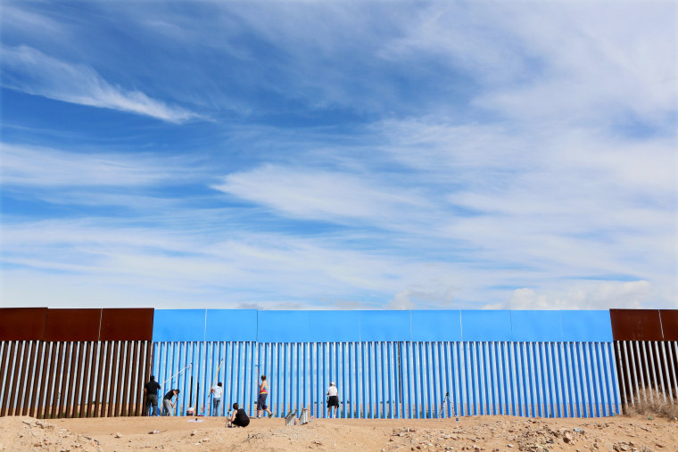 Image: Volunteers paint the border fence between the United States and Mexico to give the illusion of transparency