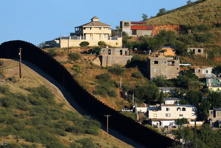 Image: Buildings in Nogales, Mexico (R) are separated by a border fence from Nogales, Arizona