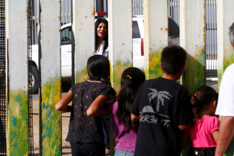 Image: A woman in Friendship Park in San Diego, California speaks with children across a fence separating Mexico and the United States, on Nov. 12, 2016.