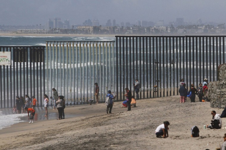 Image: People are seen next to a wall separating Mexico and the United States, as photographed from Playas Tijuana