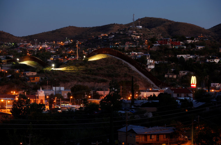 Image: A fence separates the border towns of Nogales, Mexico (R) and Nogales, Arizona, United Sates,