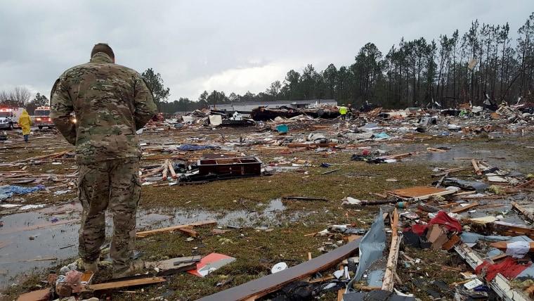 Image: A U.S. Air Force airman surveys debris covering an area of the Sunshine Acres neighborhood after the tornado struck Adel, Jan. 22.