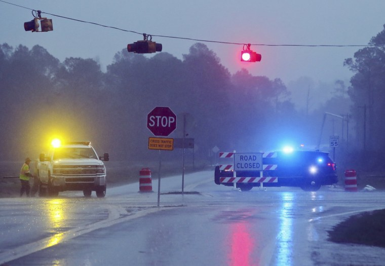 Image: A Brooks County Sheriff and officials block Highway 122 as power line workers repair a downed pole near Barney, Georgia, Jan. 22.
