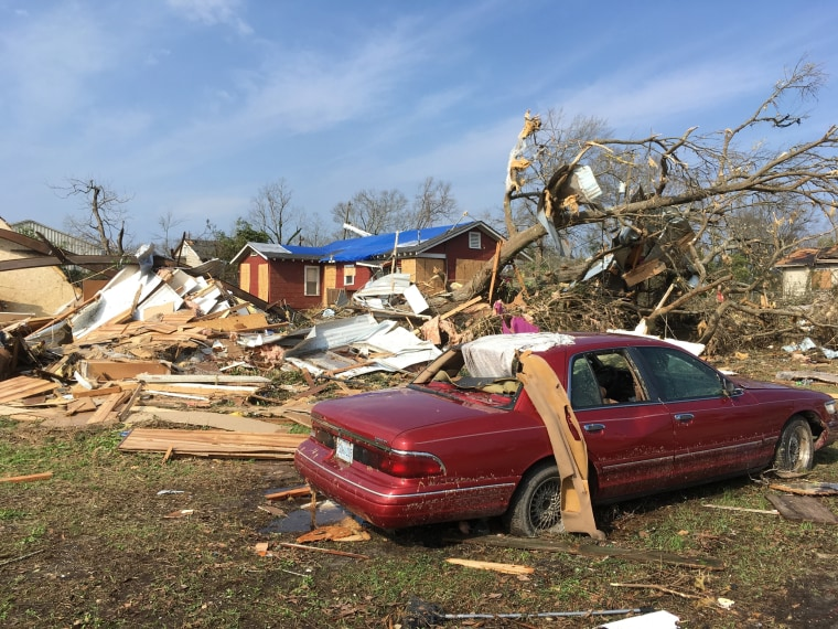 Image: A car and house are damaged at the edge of a mobile home park south of downtown Hattiesburg, Jan. 21, where one man died and others were injured.