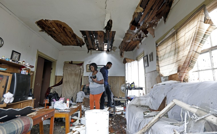 Image: Donna Thompson, and a friend, salvage some of her possessions, Jan. 21, 2017, after a morning tornado ripped her roof off in Hattiesburg.