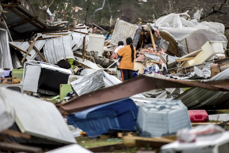 Image: A woman holds a child while walking through a damaged farm, Jan. 22, 2017, in Adel.
