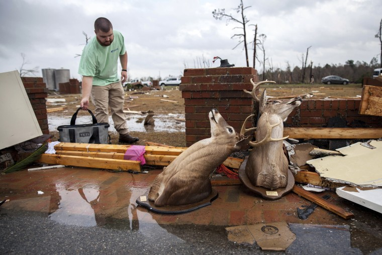 Image: Ren, who only gave his first name, cleans up at at a home that was damaged by the tornado, Jan. 22, in Adel.