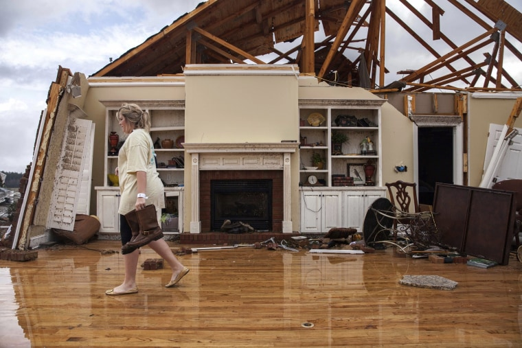 Image: Jenny Bullard carries a pair of boats from her home that was damaged by the tornado in Adel, Jan. 22.
