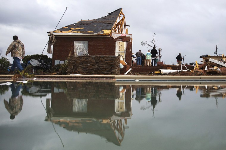 Image: People are reflected in a swimming pool as they work to clean up at a home that was damaged by a tornado in Adel, Jan. 22.