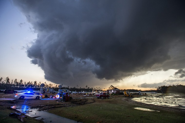 Image: Storm clouds approach emergency crews at the scene of a house cut in half by a tornado near where seven people were killed outside Adel, Georgia, on Jan. 22, 2017.