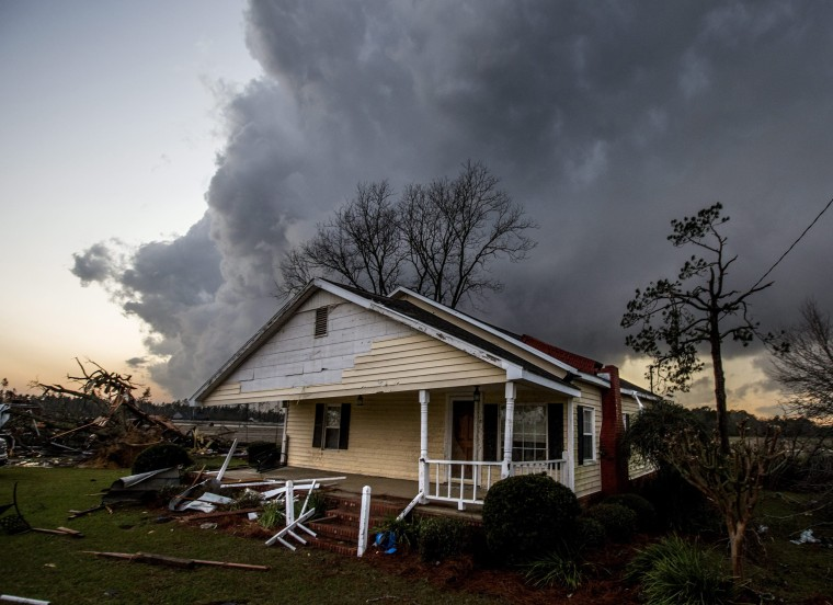 Image: A storm cloud approaches one of the homes damaged by tornadoes outside Adel on Jan. 22.