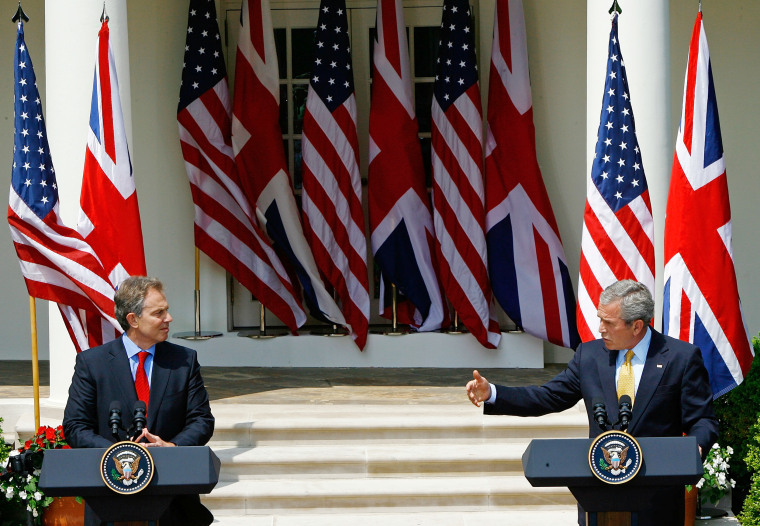 Image: British Prime Minister Tony Blair listens as President George W. Bush speaks at a news conference