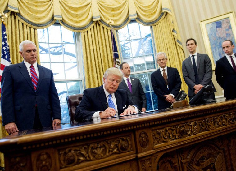 Image:  Trump signs an executive order in the Oval Office