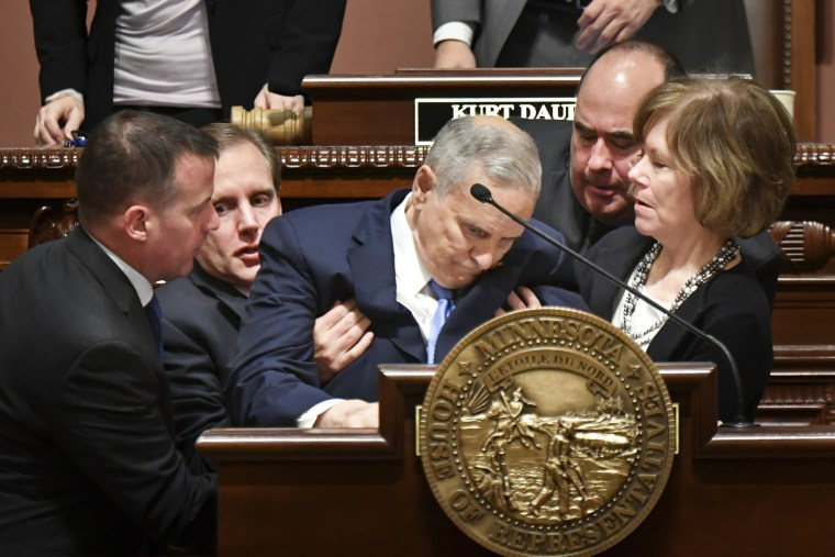 Image: Minnesota Lt. Governor Tina Smith, right, and Secretary of State Steve Simon, left, help Minnesota Gov. Mark Dayton after he collapsed during his State of the State address in St. Paul, Minnesota on Jan. 23.