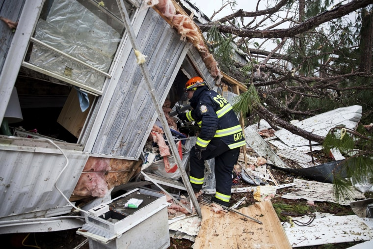 Image: A rescue worker enters a hole in the back of a mobile home, Jan. 23 in Big Pine Estates that was damaged by a tornado, in Albany, Georgia.