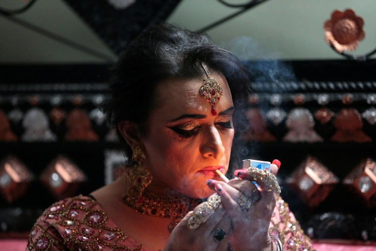 Image: Shakeela, a member of the transgender community, lights a cigarette as she prepares for her party in Peshawar