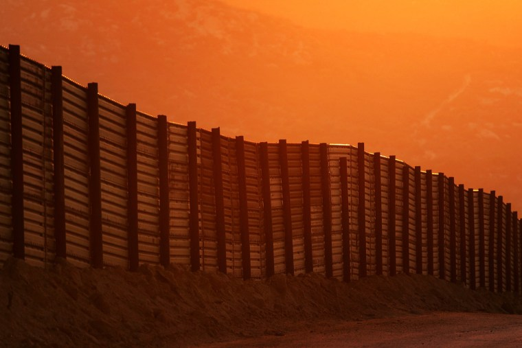 Image: Dusk falls over a section of the U.S.-Mexico border fence on Oct. 8, 2006 near Campo, California.