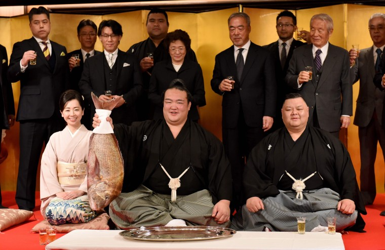 """Image: Accompanied by stable master Tagonoura (bottom-R), Tagonoura's wife (bottom-L) and supporters, sumo wrestler Kisenosato (C) holds up a big sea bream to celebrate his promotion to the top rank of """"yokozuna."""""""