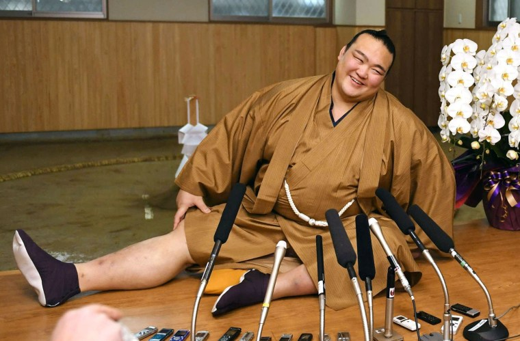 Image: New Year Grand Sumo Tournament winner ozeki Kisenosato stretches his legs during a press conference at his Tagonoura stable in Tokyo